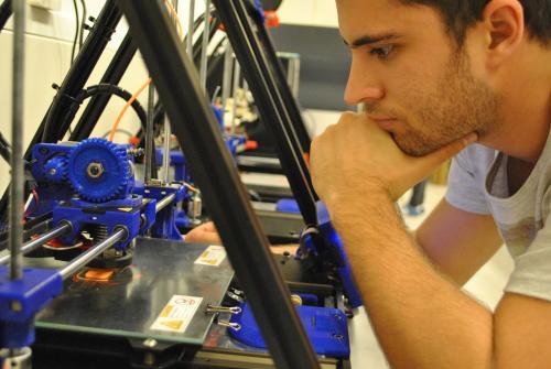 Un estudiante de la UPC trabajando con una impresora 3D en el FabLab Terrassa